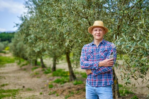 Agricultor de homem com chapéu de palha na plantação de oliveiras.