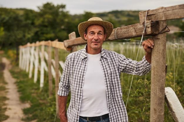 Agricultor de meia idade perto de cerca de madeira em campo rural