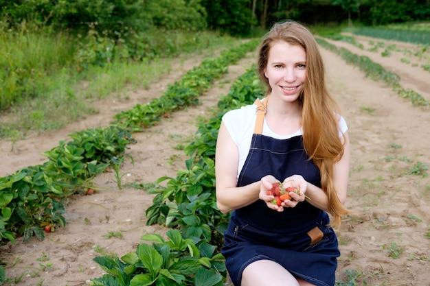 Agricultor de morango fazenda segurando uma pilha de morangos e sorrindo