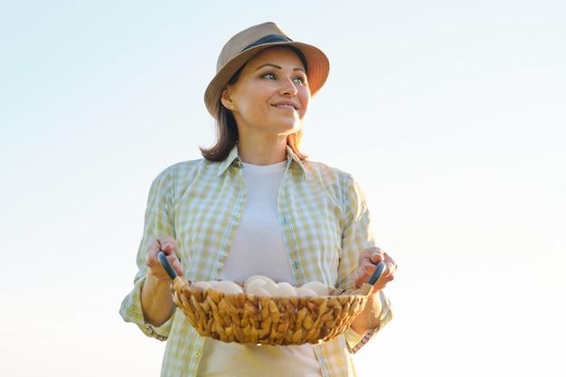 Agricultor de mulher bonita madura com cesta de ovos frescos,