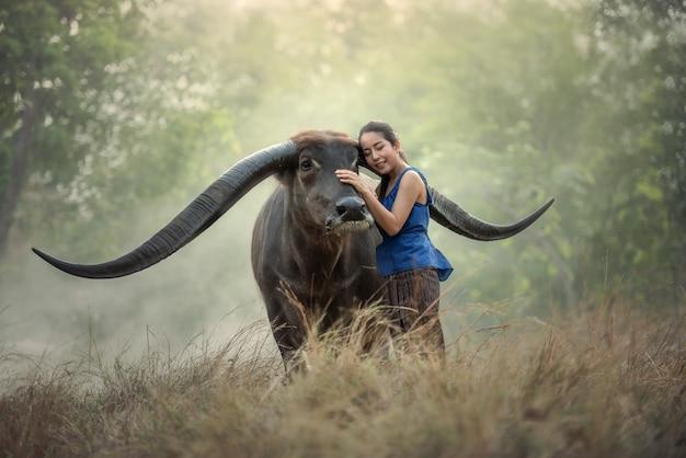 Agricultor de mulher tailandesa com búfalo