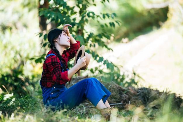 Agricultor de mulheres sentado e cansado após a colheita
