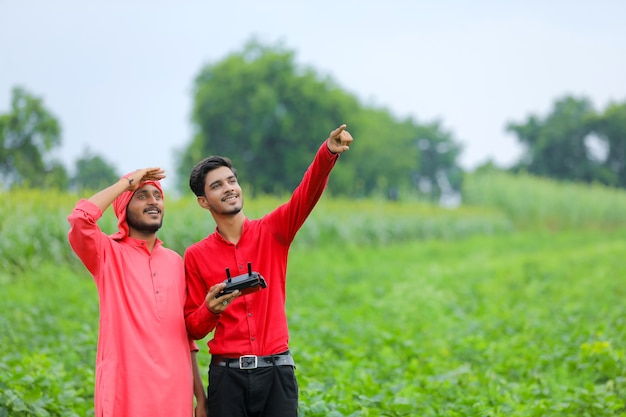 Agricultor e agrônomo indiano usando drone em campo agrícola