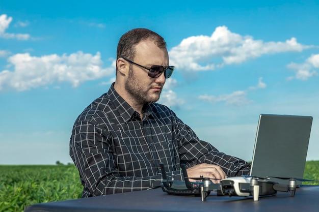 Agricultor em pé no campo de soja, olhando para o notebook e o drone.