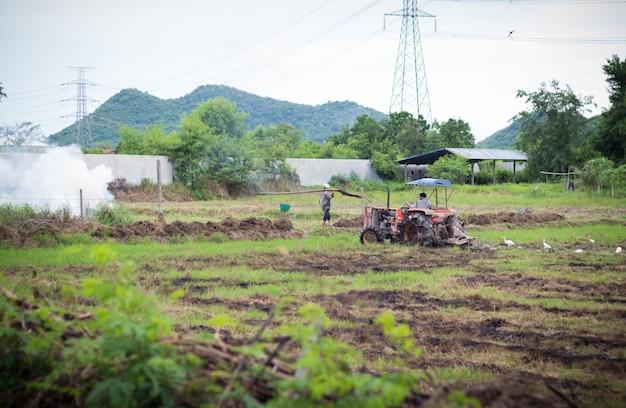 Agricultor em trator preparando terreno com cultivador de sementeira