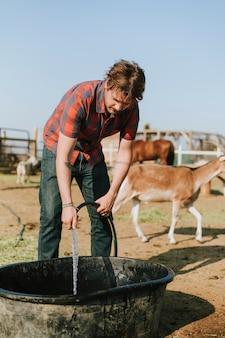 Agricultor enchendo uma banheira com água