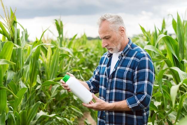 Agricultor envelhecido médio em um campo, segurando uma garrafa com fertilizantes químicos