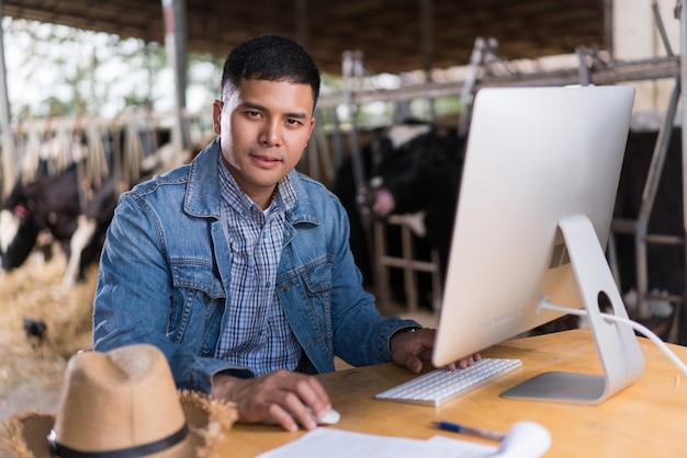 Agricultor está usando o computador para informações agrícolas. para vender leite online