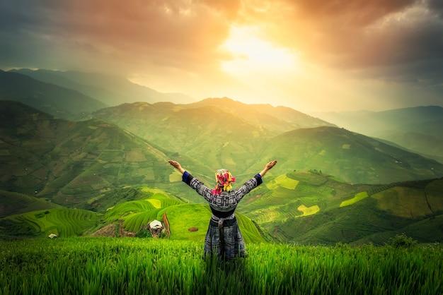 Agricultor fica no campo de paddy. e levante as duas mãos.