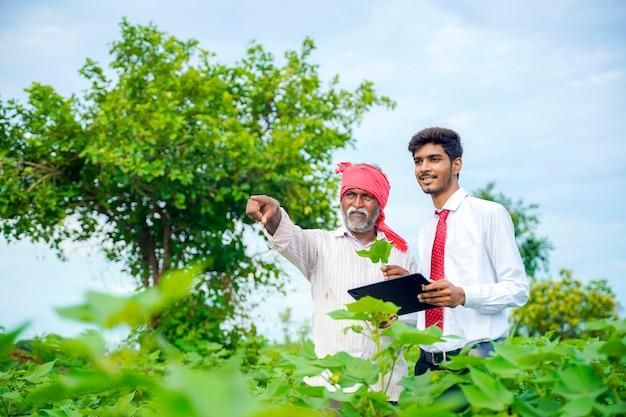 Agricultor indiano com agrônomo na plantação de algodão, mostrando algumas informações na guia