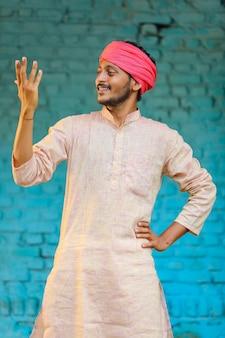 Agricultor indiano com roupas tradicionais e expressão de alegria em casa