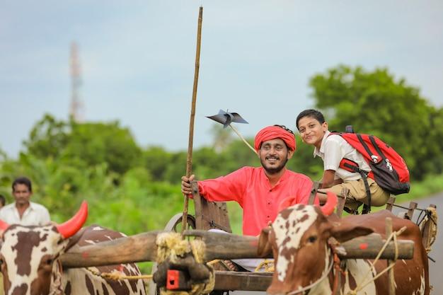 Agricultor indiano com um estudante em um carro de boi