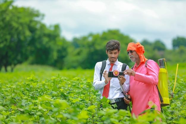 Agricultor indiano discutindo com agrônomo na fazenda e coletando algumas informações