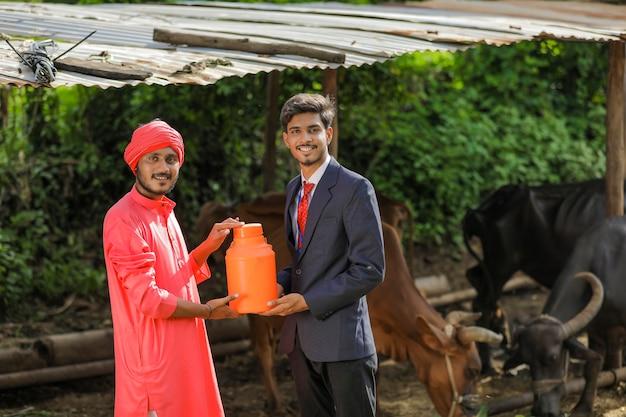 Agricultor indiano e oficial de criação de animais segurando garrafa de leite na fazenda de laticínios