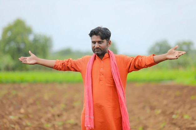 Agricultor indiano em pé e espalhando a mão no campo de agricultura.