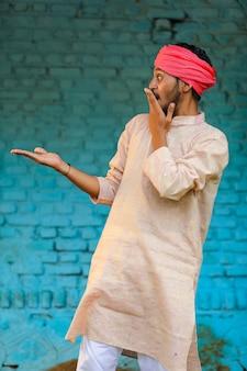 Agricultor indiano em roupas tradicionais e dando uma expressão chocante em casa