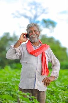 Agricultor indiano falando no celular no campo de agricultura