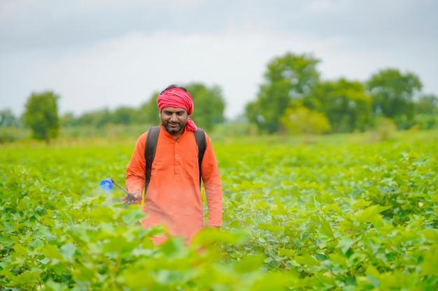 Agricultor indiano pulverizando pesticida em um campo de algodão.