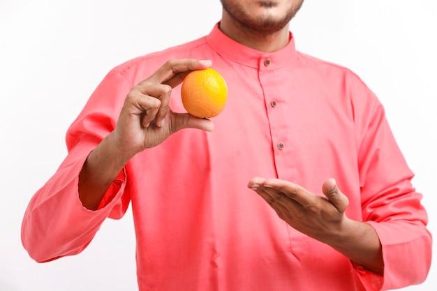 Agricultor indiano segurando uma fruta laranja na mão sobre fundo branco.