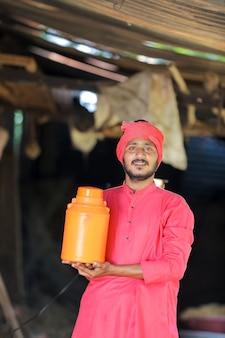 Agricultor indiano segurando uma garrafa de leite em uma fazenda de laticínios