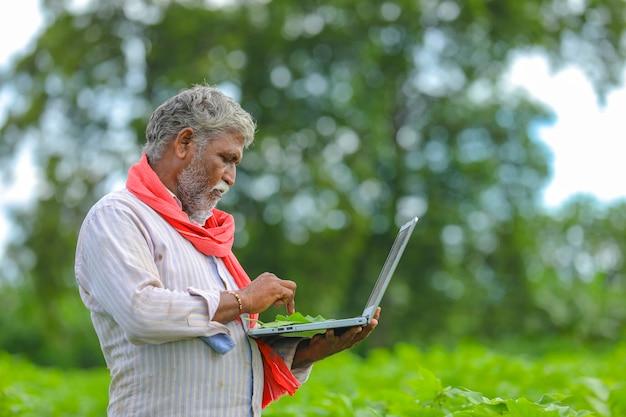 Agricultor indiano usando um laptop em um campo agrícola