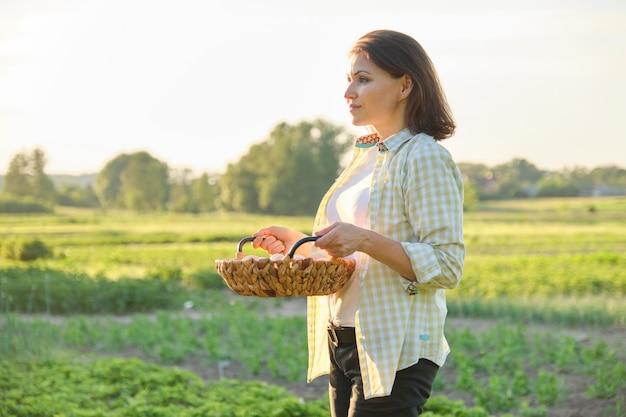 Agricultor maduro bonito da mulher com a cesta de ovos frescos