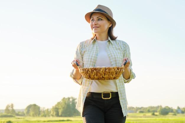 Agricultor maduro bonito da mulher com a cesta de ovos frescos,