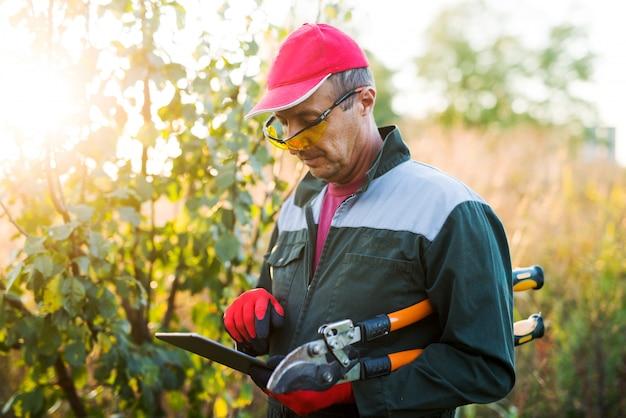 Agricultor moderno no campo com grandes tesouras, olhando para um tablet.
