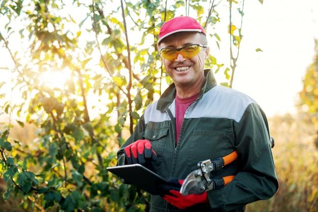 Agricultor moderno no campo com uma tesoura e um tablet