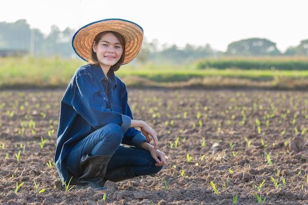 Agricultor mulher asiática vestindo jeans está sentado e olhando para as safras da fazenda com uma cara sorridente.