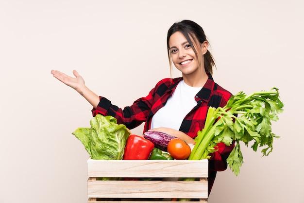 Agricultor mulher segurando legumes frescos em uma cesta de madeira, estendendo as mãos para o lado para convidar para vir