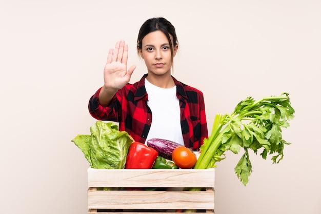 Agricultor mulher segurando legumes frescos em uma cesta de madeira, fazendo o gesto de parada com a mão
