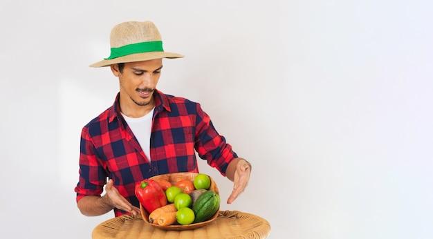 Agricultor negro com chapéu e luvas segurando uma cesta de vegetais (cenoura, limão, tomate, chuchu e beterraba) isolado no fundo branco