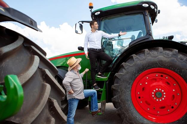 Agricultor profissional com um trator moderno combinado em um campo sob a luz do sol no trabalho