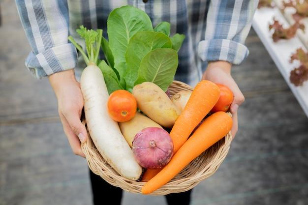 Agricultor segurando uma cesta de vegetais orgânicos. vegetais orgânicos de fazendas que estão prontos para serem exportados dos agricultores.