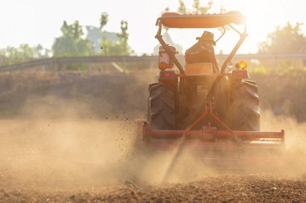 Agricultor tailandês em grande trator na terra para preparar o solo