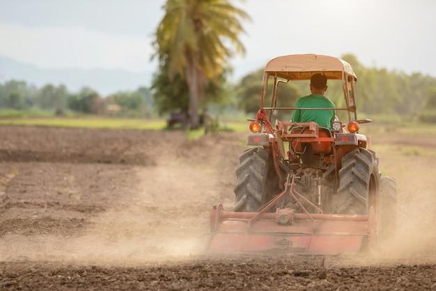 Agricultor tailandês no grande trator na terra para preparar o solo para a temporada de arroz