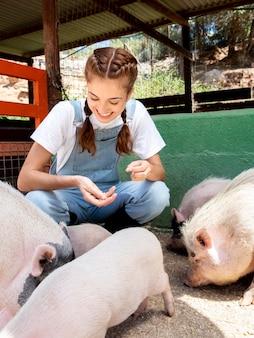 Agricultora alimentando os porcos