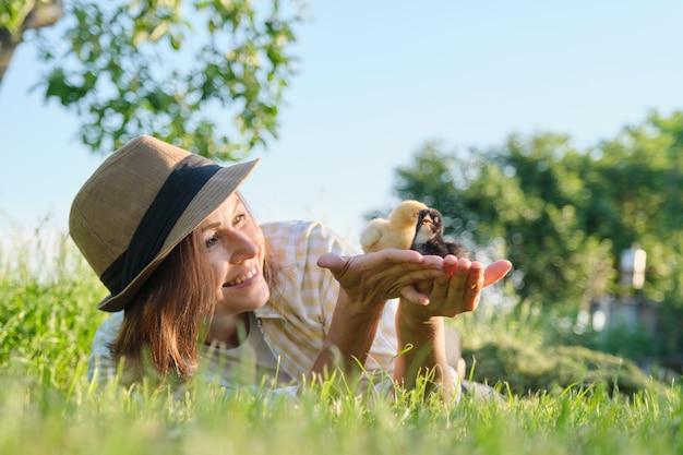 Agricultora ao ar livre, mulher madura segurando nas mãos dois pequenos pintinhos recém-nascidos