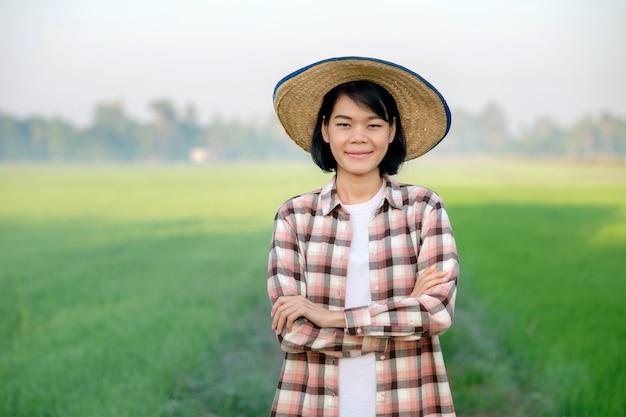 Agricultora asiática em pé com um chapéu e braços cruzados em uma fazenda de arroz verde