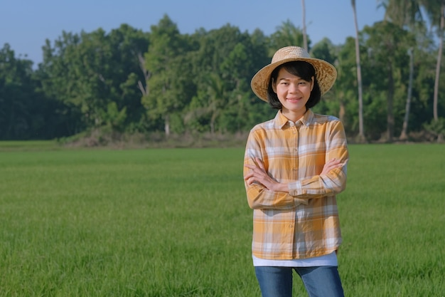 Agricultora asiática em pé e de braços cruzados em uma fazenda de arroz