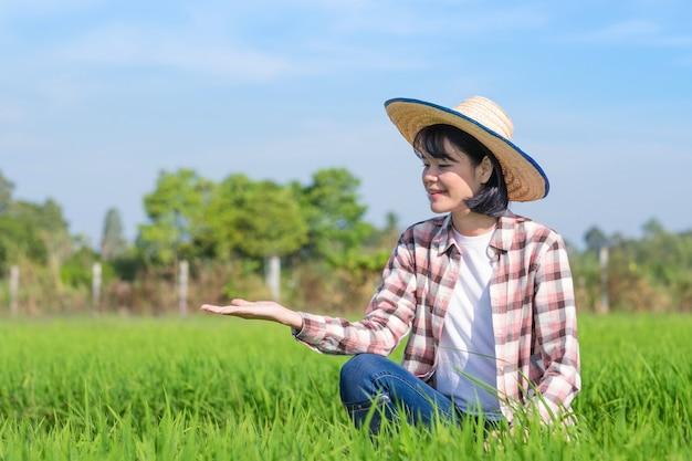 Agricultora asiática sentada e levantando a mão para presentear produtos na fazenda de arroz verde