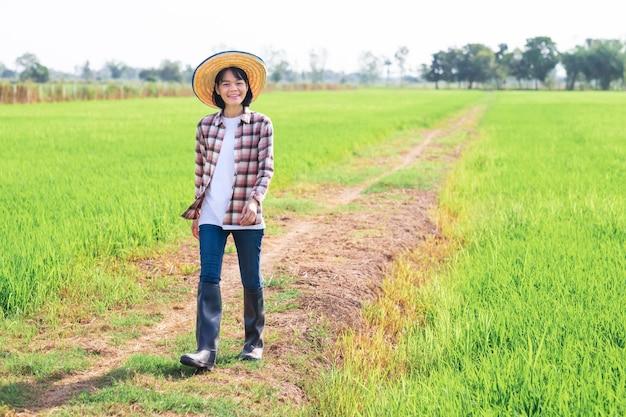 Agricultora asiática sorrindo e caminhando em uma fazenda de arroz verde