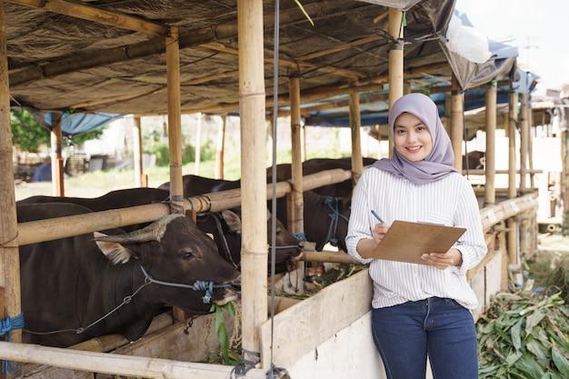 Agricultora muçulmana asiática em pé na fazenda com uma vaca