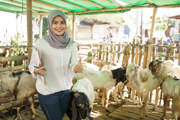 Agricultora muçulmana fazendo check-up para sua cabra na gaiola