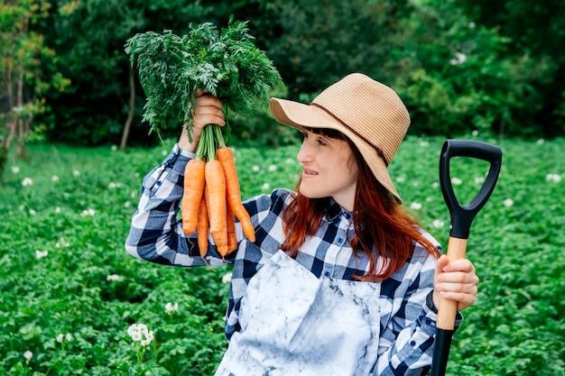 Agricultora segura um cacho de cenouras em um chapéu de palha no fundo de uma horta