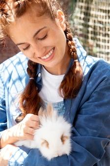 Agricultora segurando um coelhinho branco
