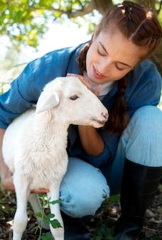 Agricultora segurando uma ovelha bebê