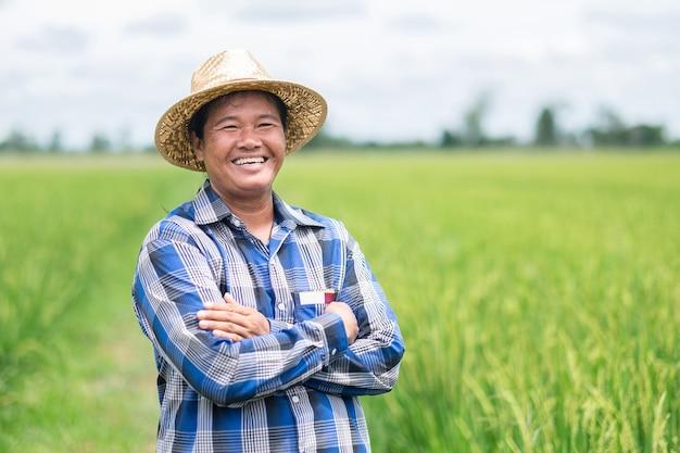 Agricultora tailandesa asiática com sorriso de camisa azul e mãos cruzadas na fazenda verde