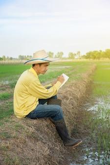 Agricultores asiáticos usam camisas amarelas sentados e escrevendo relatórios na fazenda verde.